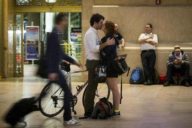 A couple kisses during the morning rush in the main concourse of Grand Central Terminal in New York May 23, 2014. (Photo by Brendan McDermid/Reuters)