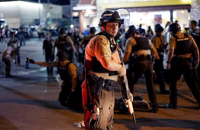 A police officer holds his weapon as a protester is detained (rear) in Ferguson, Missouri, August 10, 2015. (Photo by Rick Wilking/Reuters)