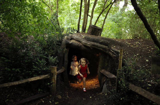 Children play inside an area designed to look like a badger set during a photocall at Kew Gardens on July 20, 2017 in London, England. The Kew Gardens Summer festival includes a newly opened 16 hectare area of the woodland and wilflower meadow. The educational activities focus on pollination, with woodland walks, a treehouse, and boardwalks. (Photo by Dan Kitwood/Getty Images)