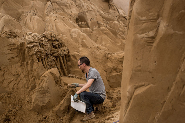 Sand sculptor Shao Jianxin of China works on sculpting a Panda at the site of Yokohama Sand Art Exhibition – Culture City of East Asia 2014 on July 16, 2014 in Yokohama, Japan. Producer and sand sculptor Katsuhiko Chaen invited artists from around the world including South Korea and China, to recreate the World Heritage and historical buildings in China, Japan and South Korea. The exhibition will be open from July 19 to November 3, 2014. (Photo by Chris McGrath/Getty Images)
