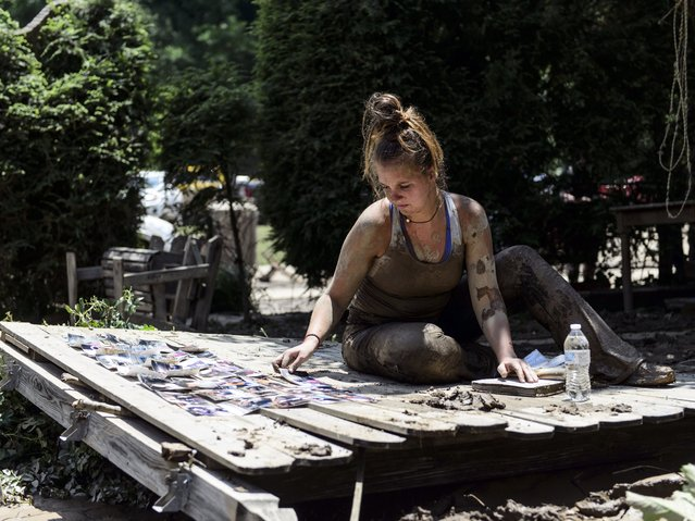 Taylor Self of Charleston lays pictures out to dry as she takes a break from cleaning Sherry and Kelly Cole's house, who are her best friend's parents, in Clendenin, W.Va., on Saturday, June 25, 2016. Self drove from Charleston early Saturday morning once she saw pictures of the damage done by flooding on Sherry Cole's Facebook page. The scene in Clendenin, located in Kanawha County, wasn't as deadly as in Ranielle. Sixteen people died in Greenbrier County, at least 15 of them in Ranielle. Greenbrier is the only county where Gov. Earl Ray Tomblin's administration believes people remain missing. (Photo by Sam Owens/Charleston Gazette-Mail via AP Photo)