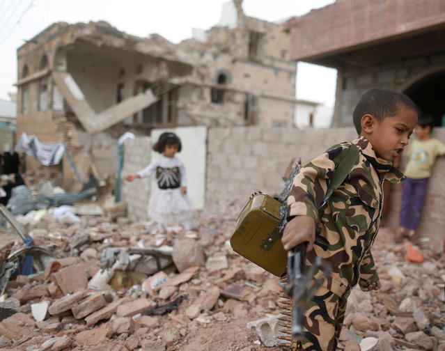 A boy carries a toy machine gun next to destroyed houses during a vigil marking one year since a Saudi-led air strike on a residential area in Sanaa, Yemen June 21, 2016. (Photo by Khaled Abdullah/Reuters)