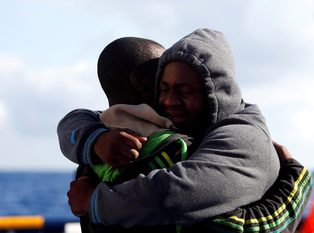 Migrants embrace on the Migrant Offshore Aid Station (MOAS) ship Topaz Responder after being rescued around 20 nautical miles off the coast of Libya, June 23, 2016. (Photo by Darrin Zammit Lupi/Reuters)