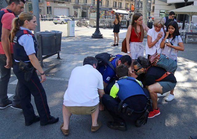 A person is treated in Barcelona, Spain, Thursday, August 17, 2017 after a white van jumped the sidewalk in the historic Las Ramblas district, crashing into a summer crowd of residents and tourists and injuring several people, police said. (Photo by Oriol Duran/AP Photo)