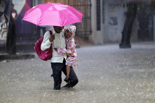 An Indian man carries a schoolgirl and wades through a waterlogged street as it rains in Mumbai, India, Thursday, July 31, 2014. Heavy rainfall in the city flooded several areas causing traffic havoc and delay in trains. (Photo by Rajanish Kakade/AP Photo)