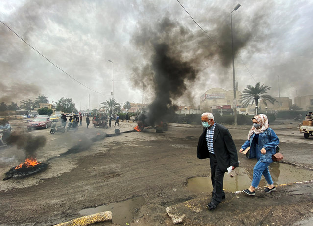 Iraqi people wear protective face masks, following the outbreak of the new coronavirus, as they walk past burning tires ignited by Iraqi protesters to block the road during ongoing anti-government protests in Nassiriya, Iraq on February 25, 2020. (Photo by Ahmed Dhahi/Reuters)