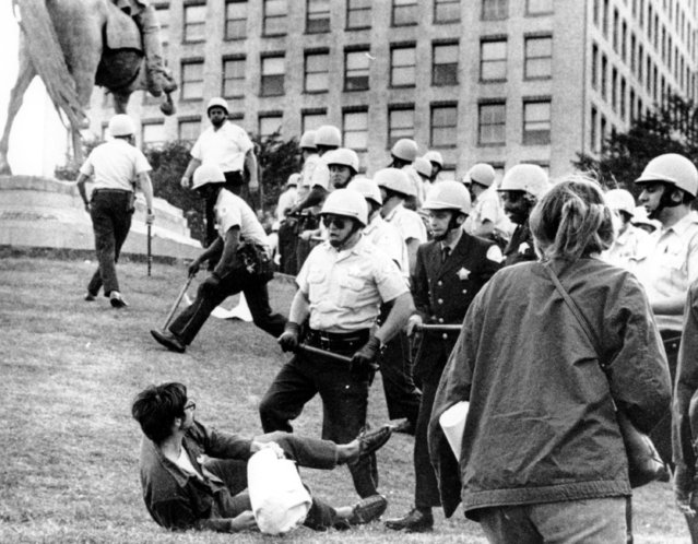 This photo shows Chicago policemen with nightsticks in hand confronting a demonstrator on the ground in Grant Park, Chicago, on August 26, 1968. The police force converged at Grant Park when protesters opposing the Vietnam War climbed on the statue of civil war Gen. John Logan. (Photo by AP Photo)