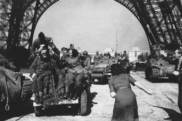 Nazi prisoners shrink from jeering Parisians as they are driven under the Eiffel Tower under the guard of the first U.S. troops to enter Paris on August 28, 1944. (Photo by AP Photo)