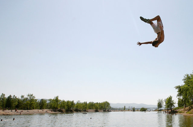 A man jumps into a lake, located on the Tatyshev Island in the middle of the Yenisei River, with the air temperature at about 30 degrees Celsius (86F) in Russia's Siberian city of Krasnoyarsk, on June 14, 2012. (Photo by Ilya Naymushin/Reuters)