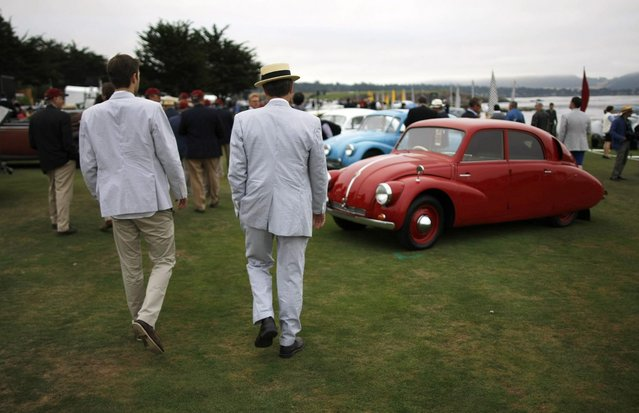 Guests walk along the 18th fairway of the Pebble Beach Golf Links during the Concours d'Elegance in Pebble Beach, California, August 17, 2014. (Photo by Michael Fiala/Reuters)
