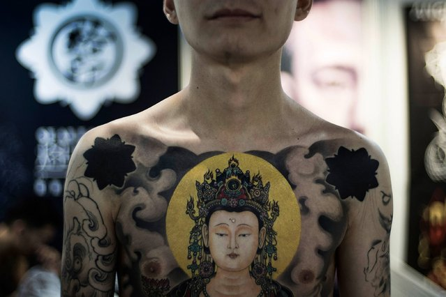 A man displays his tattoo at the Hong Kong Tattoo Convention on August 22, 2014. in Hong Kong. The 2nd International Hong Kong Tattoo Convention 2014  features tattoo artists from around the world. (Photo by Lam Yik Fei/Getty Images)