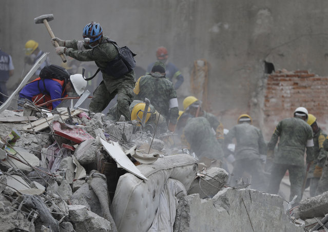 Rescue workers search for survivors at an apartment building located on the street corner of Amsterdam and Laredo, that collapsed during an earthquake in the Condesa neighborhood of Mexico City, Thursday, September 21, 2017. Tuesday's magnitude 7.1 earthquake has stunned central Mexico, killing more than 200 people as buildings collapsed in plumes of dust. (Photo by Natacha Pisarenko/AP Photo)