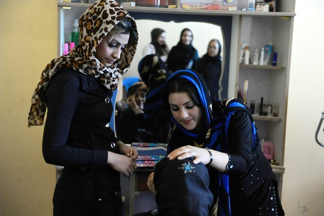 In this photograph taken on August 27, 2014  female Afghan prisoners put on make-up inside the female prison in Herat. The facility, which was built by the Italian Provincial Reconstruction Team, holds approximately 140 inmates, some with their children alongside them, whose crimes range from murder, drug trafficking to running away from home. The prison programme includes teaching inmates skills, such as carpet weaving, that will help them survive when they are released. (Photo by Aref Karimi/AFP Photo)