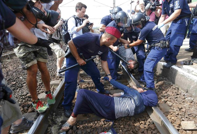 Hungarian policemen detain migrants on the tracks as they wanted to run away at the railway station in the town of Bicske, Hungary, September 3, 2015. A camp for refugees and asylum seekers is located in Bicske. (Photo by Laszlo Balogh/Reuters)