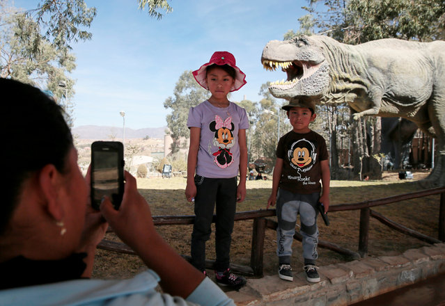 A mother takes a photograph of her children while they pose in front of the replica of a Tyrannosaurus rex at the Cretaceous park in Cal Orcko, on the outskirts of Sucre, Bolivia, July 22, 2016. (Photo by David Mercado/Reuters)