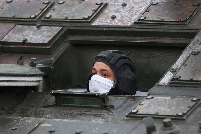 A Russian serviceman wearing a protective mask looks out of a military vehicle during a rehearsal for the Victory Day parade, amid the coronavirus disease (COVID-19) outbreak, in Yekaterinburg, Russia on April 14, 2020. (Photo by Alexei Kolchin/Reuters)