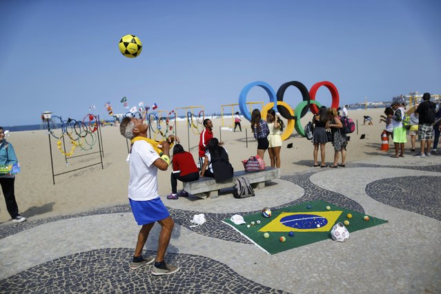 2016 Rio Olympics, Olympic Park on July 29, 2016. A street perfomer uses a football in front of the Olympic rings. (Photo by Ivan Alvarado/Reuters)