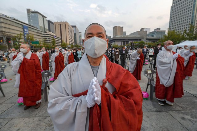 Buddhists monks wearing faces masks to help protect against the spread of the new coronavirus pray to celebrate the Buddha's birthday at the Gwanghwamun Plaza in Seoul, South Korea, Thursday, April 30, 2020. (Photo by Ahn Young-joon/AP Photo)