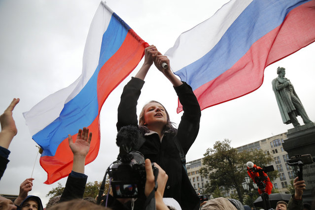 Demonstrators shout slogans and wave Russian flags during a rally in Moscow, Russia, Saturday, October 7, 2017. Opposition leader Alexei Navalny has worked to organize protests in support of his presidential bid across Russia on Saturday, President Vladimir Putin's birthday. (Photo by Alexander Zemlianichenko/AP Photo)