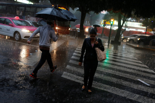 A woman crosses an avenue during heavy rain in Mexico City, Mexico, August 2, 2016. (Photo by Tomas Bravo/Reuters)