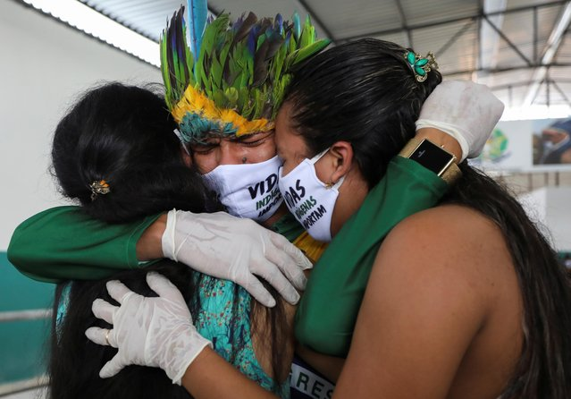 Indigenous person Miqueias Moreira Kokama, son of indigenous Chief Messias Kokama, 53, from the Parque das Tribos (Tribes Park), who passed away due to the coronavirus disease (COVID-19), reacts while embracing relatives during his father's funeral at Parque das Tribos in Manaus, Brazil, May 14, 2020. (Photo by Bruno Kelly/Reuters)