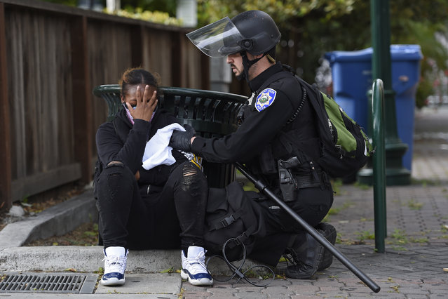 A Walnut Creek Police officer applies pressure to a bullet wound after a young female was shot in the left arm at the corner of Olympic Blvd. and Locust Street in downtown Walnut Creek, Calif., on Sunday, May 31, 2020. The shooting victim was shot by someone in a vehicle that sped away from the scene. The victim was transported to John Muir Medical Center for treatment. (Photo by Jose Carlos Fajardo/Bay Area News Group)