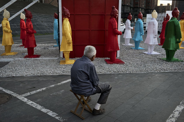 A Chinese penshioner sits on his portable bench as he looks at clourful statues replicating China's famous Terracotta Warriors are covered in plastic before being placed at an exhibtion on September 3, 2014 in Beijing, China. (Photo by Kevin Frayer/Getty Images)