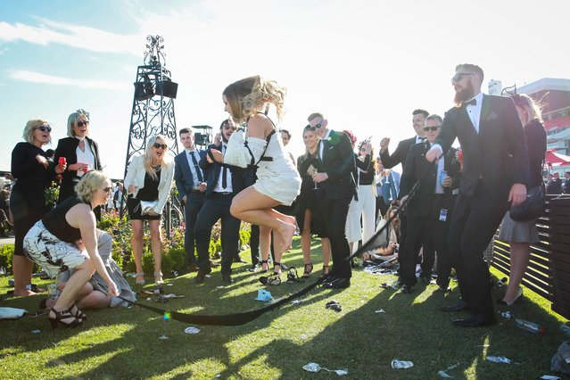 A woman leaps in the air and two pals swing a makeshift skipping rope on 2017 Derby Day at Flemington Racecourse on November 4, 2017 in Melbourne, Australia. (Photo by Splash News and Pictures)