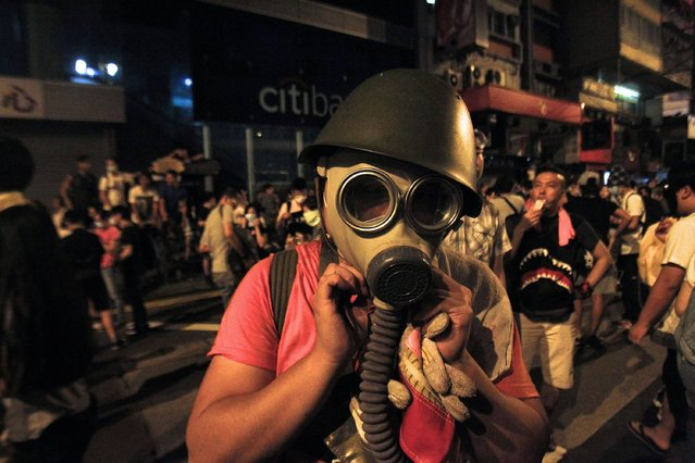 A protester puts on a gas mask to prepare for a possible tear gas attack as hundreds of protesters block a main road at Hong Kong's shopping Mongkok district September 29, 2014. (Photo by Liau Chung-ren/Reuters)