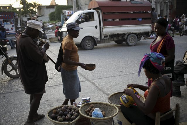 A woman begs for money as she guides a blind man in a street in Port-au-Prince, Haiti, March 7, 2016. (Photo by Andres Martinez Casares/Reuters)
