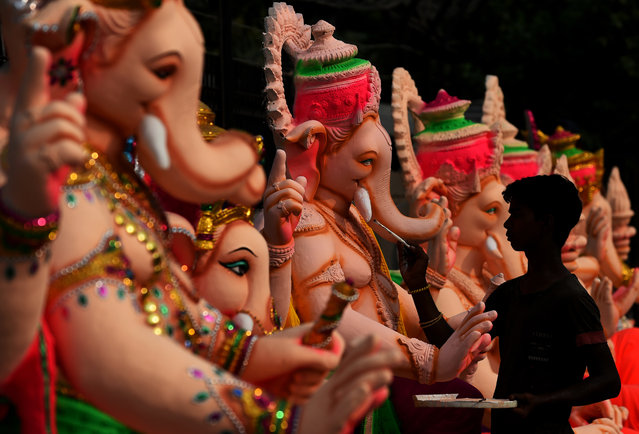 An Indian artist gives the finishing touches to a figure of the elephant-headed Hindu god Ganesha at a workshop ahead of the Ganesh Chaturthi festival in New Delhi on September 15, 2015. (Photo by Sajjad Hussain/AFP Photo)