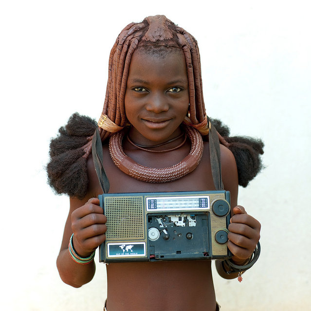 """Himba girl with her radio – Angola. She was walking with her radio around the neck. The tape was broken, but the radio was still working. In the same time, we queue for Ipad, iphod, iphone!"". (Eric Lafforgue)"