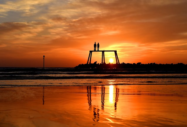 The sun rises over the north sea as The Couple by artist Sean Henery sits just of the coast at Newbiggin-by-the-Sea, England, Wednesday October 8, 2014. (Photo by Owen Humphreys/AP Photo/PA Wire)