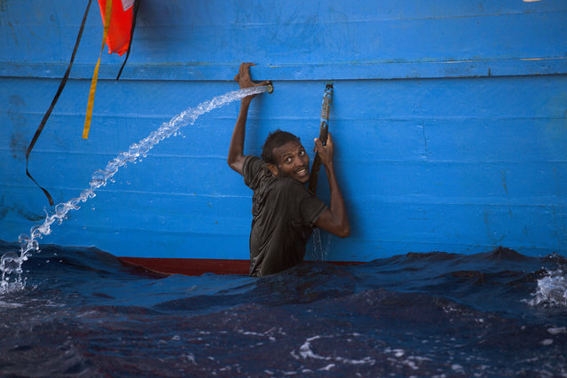 A man holds himself on the side of  a boat after jumping into the sea from a crowded wooden boat during a rescue operation at the Mediterranean sea, about 13 miles north of Sabratha, Libya, Monday, August 29, 2016. (Photo by Emilio Morenatti/AP Photo)