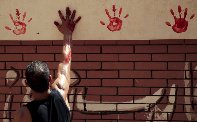 A butcher makes a hand print on the wall from the blood of a just-slaughtered calf on the first day of Eid al-Adha festival in Toukh, El-Kalubia governorate, northeast of Cairo, Egypt, September 24, 2015. (Photo by Amr Abdallah Dalsh/Reuters)