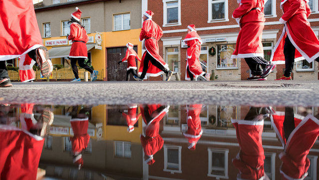 Participants dressed in Father Christmas costumes take part in the traditional Santa Claus run in Michendorf, eastern Germany, on December 10, 2017. (Photo by Ralf Hirschberger/AFP Photo/DPA)