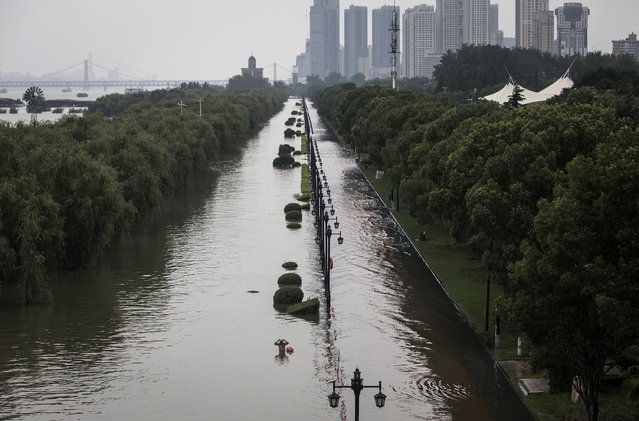 A swimmer wades through flooded water in Jiangtan park, caused by heavy rains along the Yangtze river, on July 13, 2020 in Wuhan,China. The water level at Hankou station on the Wuhan section of the Yangtze River has reached 28.77 meters, the fourth highest in history. (Photo by Getty Images)