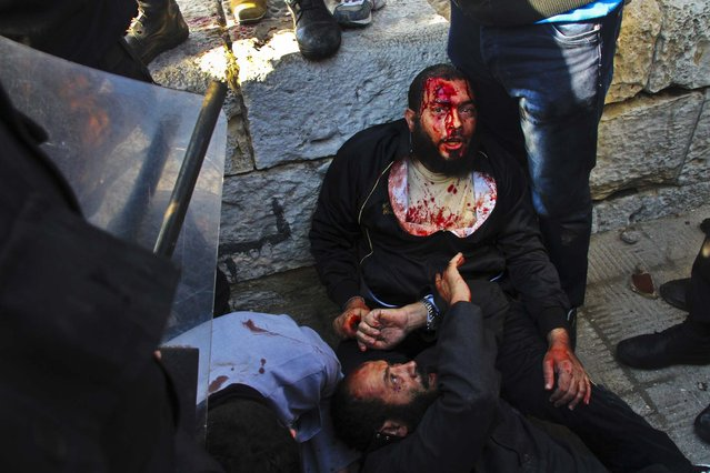 An injured men takes shelter during clashes between supporters and opponents of President Mohammed Morsi in Alexandria, Egypt, December 14, 2012. (Photo by Ahmed Ramadan/Associated Press)
