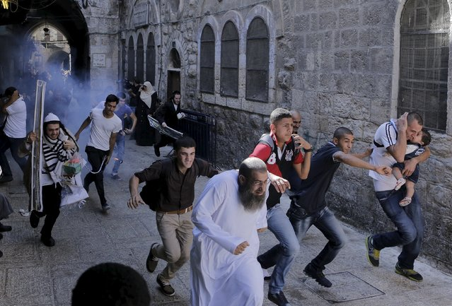 Palestinian protesters run away as Israeli police throw a stun grenade in Jerusalem's Old City September 28, 2015. (Photo by Ammar Awad/Reuters)
