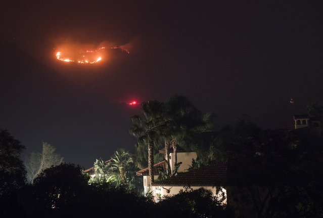 Fire burns in the hills behind a home at the Thomas Fire, December 16, 2017 in Montecito, California. (Photo by Robyn Beck/AFP Photo)