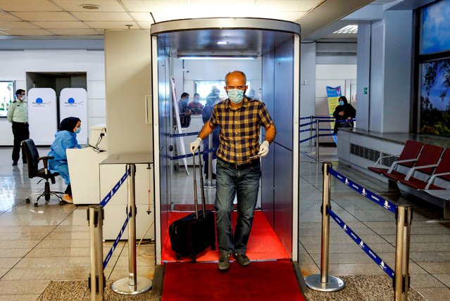 An incoming passenger crosses with his luggage through a disinfection tunnel upon arriving on an Emirates flight at the Iranian capital Tehran's Imam Khomeini International Airport on July 17, 2020. The UAE's Emirates airlines landed its first flight in Tehran on July 17 after a six month shutdown due to the novel coronavirus pandemic. (Photo by AFP Photo/Stringer)