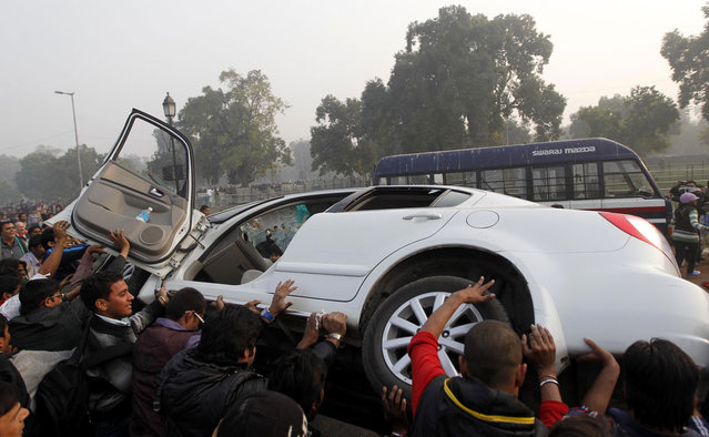 Indian protestors damage a government vehicle during a violent demonstration near the India Gate monument in New Delhi, on December 23, 2012. (Photo by Mustafa Quraishi/AP Photo)