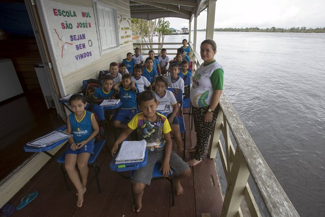 Children of the floating Municipal School Sao Jose II pose for a picture along the Amazonas River bank in a rural area of Manaus, Brazil, June 18, 2015. (Photo by Bruno Kelly/Reuters)