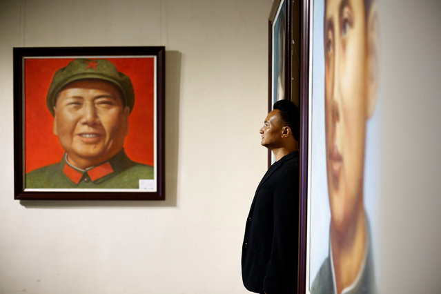 A man poses in front of portraits of late Chinese Chairman Mao Zedong during the opening of an exhibition of Mao related art in Beijing, China, September 8, 2016. (Photo by Thomas Peter/Reuters)