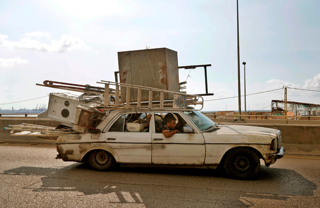 A man drives a car loaded with electronic and household appliances the Dbayeh highway, at the northern entrance of Lebanon's capital Beirut, on August 11, 2020, following a huge chemical explosion that devastated large parts of the city. (Photo by Joseph Eid/AFP Photo)