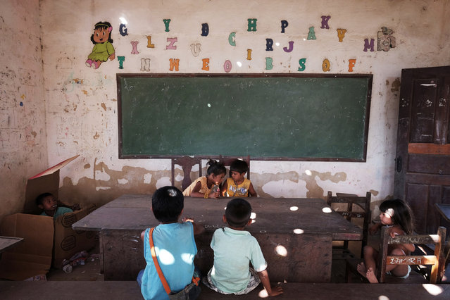 Children play in a school room in Cigana Village of in Araribóia Indigenous Reserve, Maranhão, Brazil on August 8, 2015. Members of the community are upset about the condition of the school and since there are few jobs the village allows loggers to pass through - for a fee - despite efforts by the Guardians of the Forest to persude them otherwise. Loggers have been stealing hardwood trees from indigenous lands in Brazil. The Guardians of the Forest are an armed militia formed by the Guajajara tribe to protect their reserve. (Photo by Bonnie Jo Mount/The Washington Post)