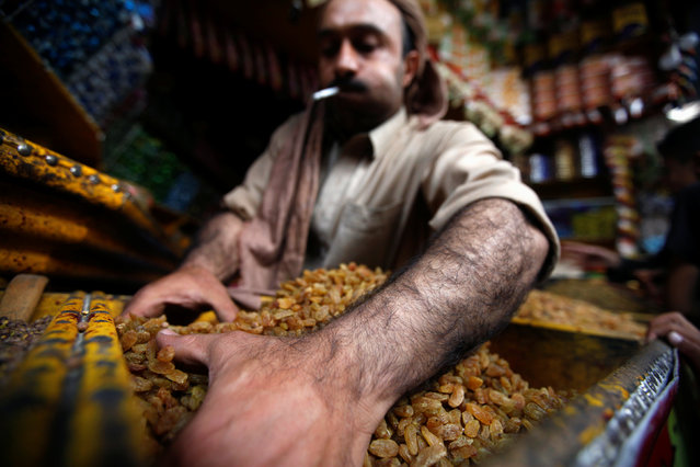 A man displays raisins in his shop, ahead of Eid Al-Adha festival, in the old market of the historic city of Sanaa, Yemen September 11, 2016. (Photo by Mohamed al-Sayaghi/Reuters)