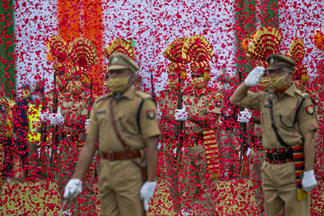Flower petals fall on Indian paramilitary soldiers participating in an Independence Day parade in Gauhati, India, Saturday, August 15, 2020. India's prime minister said Saturday his country has done well in containing the coronavirus pandemic and announced $1.46 trillion infrastructure projects to boost the sagging economy. (Photo by Anupam Nath/AP Photo)