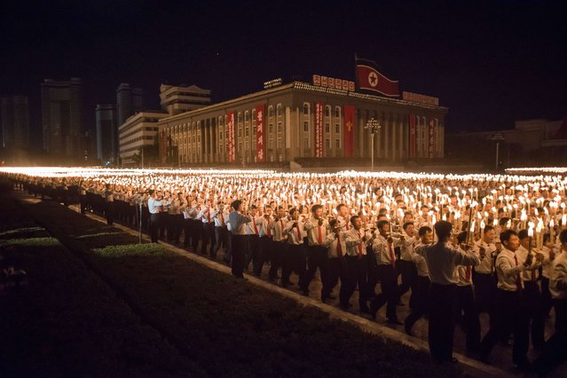North Korean volunteer performers take part in a torch-light performance in Pyongyang on October 10, 2015. (Photo by Ed Jones/AFP Photo)