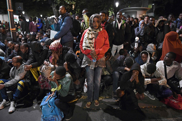 Migrants gather and wait before being evacuated from a makeshift migrant camp set up between the metro stations of Jaures and Stalingrad, in Paris, on September 16, 2016. (Photo by Christophe Archambault/AFP Photo)
